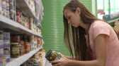 консервы : Young woman picking canned food from the shelves at supermarket and reading the label