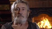 grizzled : Portrait senior man with grey hair looking at camera alone at home near the fireplace, slow motion 60 fps