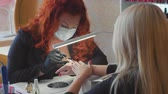Professional gel polish manicure. Female red hair master in the salon makes a spa procedure for the fingernails of the blonde client. Beauty industry, relax concept.