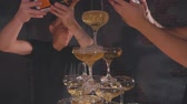 banquette : Two waiters pouring champagne in wineglasses at pyramid. Champagne glasses at the party. Pyramid of champagne close-up in slow motion. Festive alcohol . Collective drunkenness.