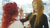Beautiful girl artist with halloween makeup at work. Process applying halloween makeup on models face. Artist working and dancing slow motion.