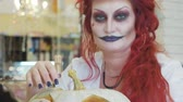 Portrait of redhead woman with halloween makeup in nurse stile with pumpkin in slow motion.
