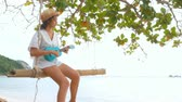 Asian woman playing Ukulele at beach. Single and Happiness concept. Nature and sea theme. Musical instrument and Vintage theme. Vídeos