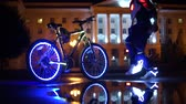 Glowing bicycle is reflected in the water. A man in glowing shoes dances around a futuristic bike.
