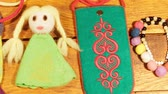 Bag, doll and decoration of felt wool on a wooden background. Childrens creativity