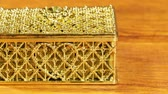 Closed jewelry box for decorations with a heart pattern on a wooden table.