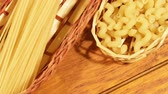 Raw unprepared pasta on wooden boards. Pasta in basket on wooden background Stock Footage