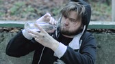 Portrait of young alcoholic, drunk man drinking vodka in outdoor