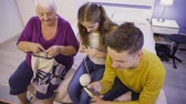 People, Old Woman, Girl, Boy, Family Portrait The woman knits on the needles, the guy with the smartphone online. Stock Footage