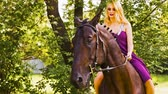 riders : A young woman in a beautiful dress in a green square and learns to ride a horse. Stock Footage