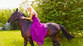 A young woman in a beautiful dress in a green square and learns to ride a horse. Stockvideo