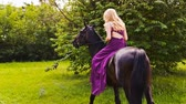 moda : A young woman in a beautiful dress in a green square and learns to ride a horse. Stok Video