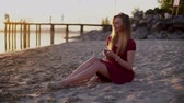 Smartphone woman in red dress sms texting using app on smart phone at beach sunset. Stock Footage