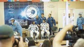 BAIKONUR, KAZAKHSTAN - JULE 28: Three live real cosmonauts go to the rocket, say goodbye to a crowd of people, wave their hands. Dressed in a space suit. Launch of the Soyuz FG MS-05 space rocket.