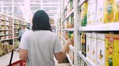 UFA RUSSIA - 30.08.2017: Woman chooses juice in the supermarket. Woman Choosing Products in Shopping Mall. Girl stands near the store shelf and selects the products Stock Footage