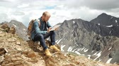 communication : mans hands touching screen of digital tablet on the background of mountains Stock Footage
