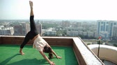 meditation : Yoga and meditation in a modern city. Young woman doing yoga on the roof. 4k