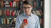 knihovna : young man portrait using smartphone laughing standing in library social media funny