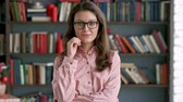 застенчивый : close up portrait of young pretty librarian woman smiling happy looking at camera in library bookshelf background knowledge learning