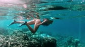 diving equipment : Young lady snorkeling over coral reefs in a tropical sea. Woman with mask snorkeling in clear water