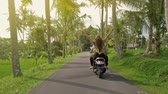 lambreta : Couple riding their scooter through forest. life style idea concept. Young beautiful couple rides the jungle on a scooter, travel, freedom, happiness, vacation, honeymoon concept