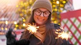 wandelstok : Women with sparklers in their hands that bokeh cities centre background. Outdoor of young beautiful happy smiling girl holding sparkler, walking on street. Stockvideo