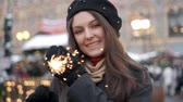 Бенгалия : Cheerful young woman holding sparklers in hand outdoor. Detail of girl celebrating new year s eve with bengal light. Closeup of beautiful woman holding a sparkling stick at bokeh cities centre