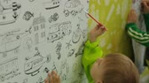 Kids drawing on wallpaper with paints Vídeos