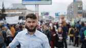 transação : Young adult angry man goes and shouts in a megaphone on strike. Caucasian guy with a beard yelling into the loudspeaker at the rally. Office worker displeased with dismissal or reduction slow mo..
