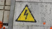 지저분한 : Sign of danger of electric shock rotates close-up rotate. Yellow designation of high voltage on the door close-up spin. Old age generalized kraaska. Dirty building 4k swirling. Sign danger and caution
