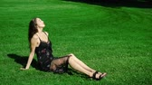 parques : Young beautiful girl model sitting on green grass of park. Woman on summer sunny day basking in sun. man is happy to sit on grass under sun. Pretty girl 20s old in dress dreams in park in afternoon