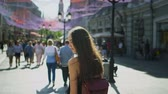 húszas évek : The girl walks along the street of a populous city in slow motion. woman turns and looks at camera while walking in afternoon along city street. girl smiles at camera and offers to follow me