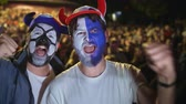 jubel : Football fan shouts, rejoices goal favorite 4K team. Man paint face jump in delight victory match. Closeup guy screaming furiously, jumping with friend against backdrop crowd winning football game Stock Footage
