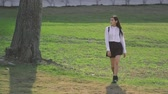 kilépő : Japanese girl walking through field in slow motion. Bird flies behind people. Yong lady looking from sidy by side and smile. Female goes proudly in slowmo. Weather is great and nature is blooms.