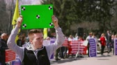 kaartjes : Man near people on strike standing hold greenscreen banner. Empty poster with tracking points in persons hands. Demonstration in middle of day. Serious and sad guy with clear placard for copyspace 4k