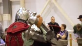 reencenação : Middle Age Knight Perform Battle Convention Center. Medieval Man in Metal Armor, Helmet Fight with Sword and Shield Slowmotion. Knighthood Chivalry Performance Footage Shot in 4K (UHD) Vídeos