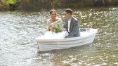 bruidspaar : Happy husband and wife are sitting in a boat and laughing at their joyful life. Nature around is incredibly beautiful and great. Newlyweds are happy to be together and swim forward to an exciting love