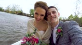 bruidspaar : Newlyweds are riding the boat by the pond and making bright selfies. Close up. Beautiful bride is holds a bouquet of roses and peones, the groom is smiling radiantly and laughs while looking at camera