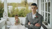 ожидая : Insanely handsome groom stands on the terrace with an important view. He is going to marry. Right behind him his beautiful wife sits on a bench. The girl has a bouquet of fragrant flowers in her hands Стоковые видеозаписи