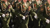 felvonulás : Parade military men demonstrate army rifles closeup slow mo step into rhythm. platoon military army marche street slowmotion. Soldier army uniform with machine gun hand close up marching formation