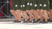 stopy : Military women march in parade in green uniform in slow motion the town square. Close-up of a female march shoes a clone of steps on the road. Feminism building women in the parade of victory