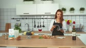 dergi : Attractive Young Woman Cooking in Home Kitchen. Smiling Redhead Girl Wearing Apron Standing at Counter. Caucasian Hostess Flipping through Magazine or Recipe Book Slowmotion. Footage Shot in 4K Stok Video