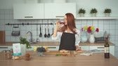 kırmızı şarap : Beautiful Woman Drinking Wine. Domestic Kitchen. Happy Ginger Beauty in Apron Standing at Counter. Caucasian Redhead Lady take Sip from Goblet Looking at Camera with Charming Smile Slowmotion. Footage
