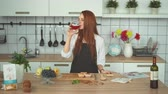 kırmızı şarap : Beautiful Woman Trying Red Wine at Modern Kitchen. Happy Redhead Caucasian Girl in Apron Enjoing Beverage. Young Lady with Goblet in Hand Looking at Camera Smiling. Footage Shot Full HD 1080p Stok Video