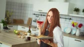 kırmızı şarap : Ginger Woman Reading Culinary Book in Kitchen. Young Caucasian Beauty Enjoy Glass of Wine while Browsing though Cookbook. Happy Cheerful Girl Sight in Camera. Footage Shot Full HD 1080p