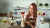 kırmızı şarap : Woman with Goblet Reading Culinary Book in Kitchen. Redhead Girl Holding Glass of Alcohol Beverage while Browsing though Cookbook. Quick Cheerful Sight in Camera. Hand Held Shot. Footage Shot in 4K