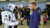 электроника : Robot cyber exhibition make gesture with man to beat off fist 4K. Demonstration of new technologies in cyber development for human life. Artificial intelligence show friendship with person in showroom
