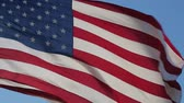 memorial : American flag is flying in the wind on a sunny day. Symbol of the Amenrican national holiday. Shooting close-up. Independence Day - American concept. Waving United States of America flag. Stock Footage