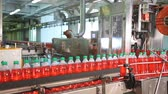 engarrafado : Production of drinking water and beverages. Fast moving PET bottles inside factory production line. Automatic conveyor line for filling water and juice in a plastic bottle.