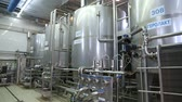 обязательство : Production tanks, storages at dairy. Pipeline at dairy factory. Huge tanks for storing and fermenting milk at a dairy factory. Panoramic shooting.